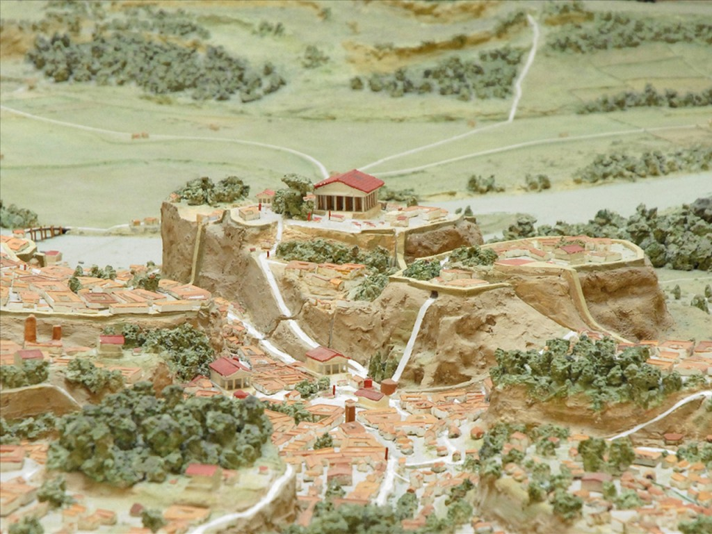 A more developed form of the settlement.  The Temple of Jupiter with its red roof still stands on the Capitoline hill, while buildings have now filled the valleys below.